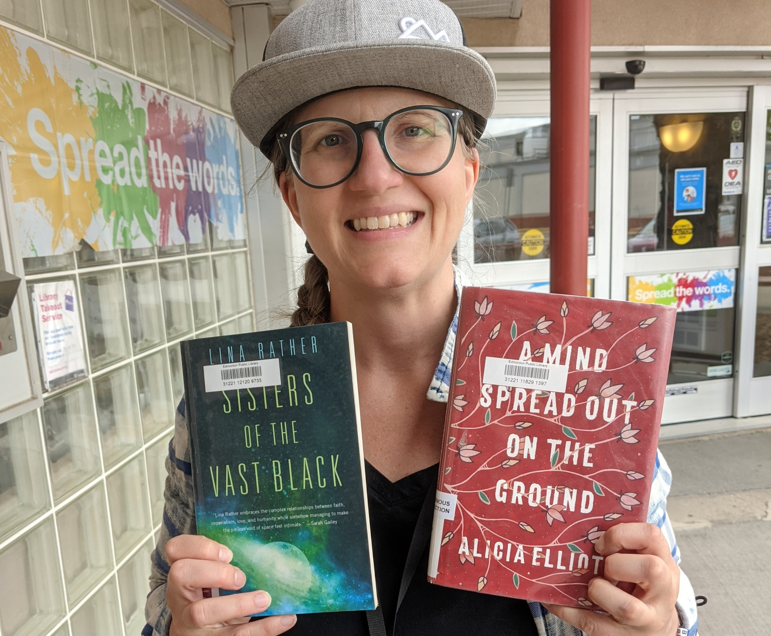 a woman wearing a grey ball cap and blue round glasses is holding up two books to the camera. the book on the left has an image of outerspace on it. the book on the right is a rich red colour with dainty drawings of leaves and flowers on it with a white title filling most of the cover.
